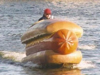 Phil Hellmuth riding a giant hot dog on water