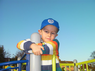 thoughtful pensive boy on park climbing frame, blue sky