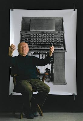 Oskar Sala ante una fotografía del Mixturtrautonium, un instrumento electrónico único originalmente desarrollado por Friedrich Trautwein