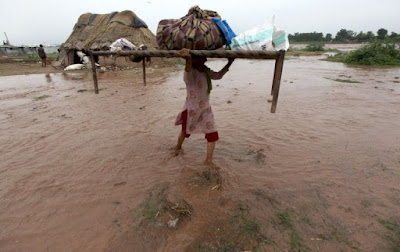 An Indian villager carrying her belongings during flash flood
