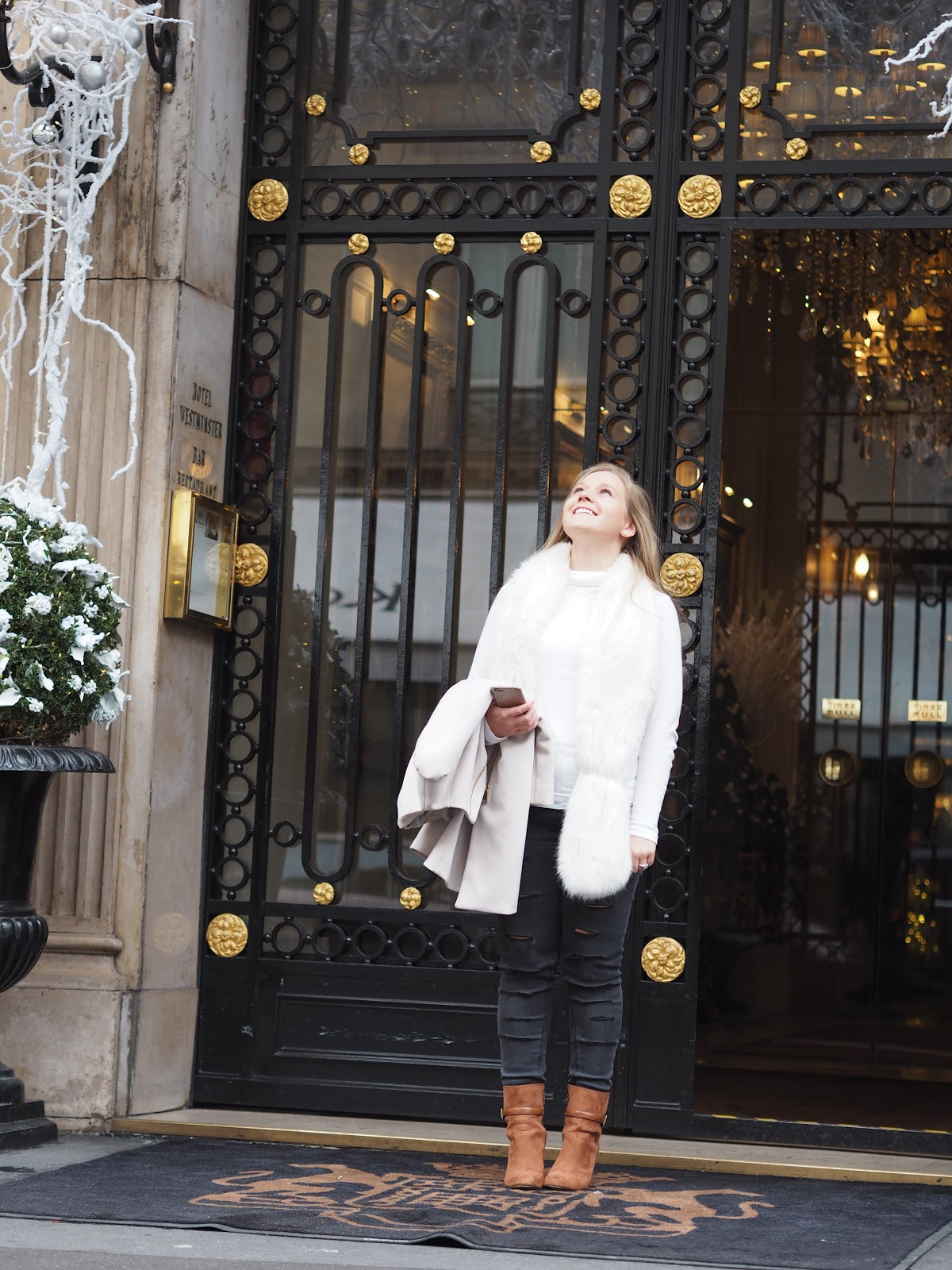 blonde girl standing outside doors of Hotel Westminster, Paris