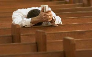 man praying whole heartedly in the church while holding bible