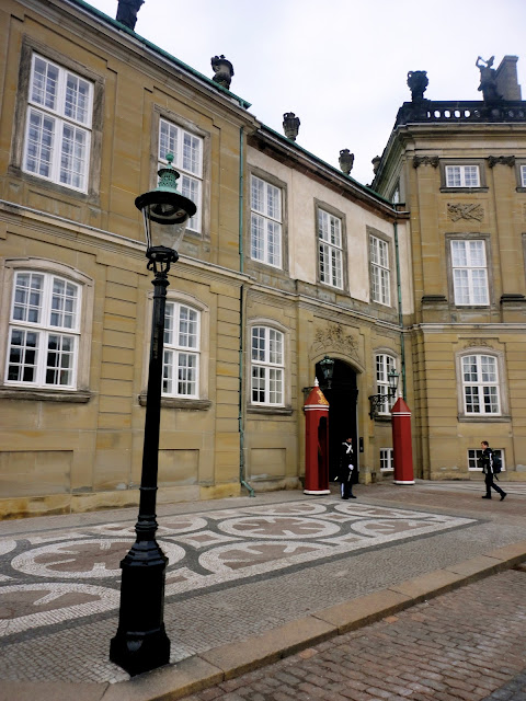 Close up of Amalienborg Palace, with guard and lamp post, in Copenhagen, Denmark