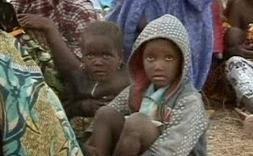 Nigerian children sit stunned in the aftermath of Boko Haram's mass killing spree. (Screen captured from YouTube video)