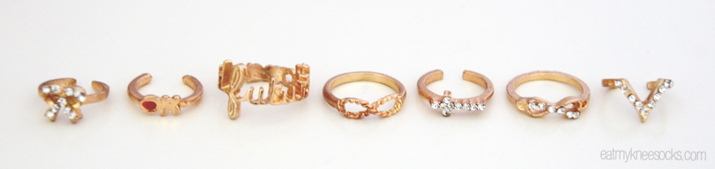 The individual rings from Born Pretty Store's 7 piece set, including a bow, a cross, infinity symbols, an arrow, and words with rhinestones.