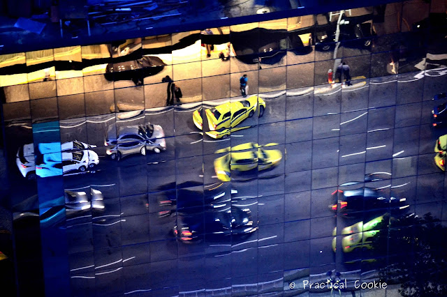 Reflections of cars on the street in the building opposite me.