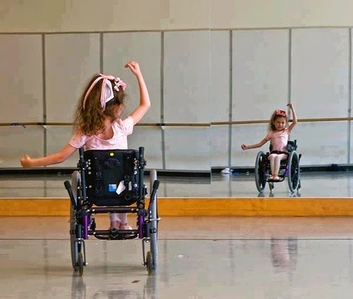 Young girl in a wheelchair doing ballet-style arm movements, viewed from behind, with front reflection in a wall mirror