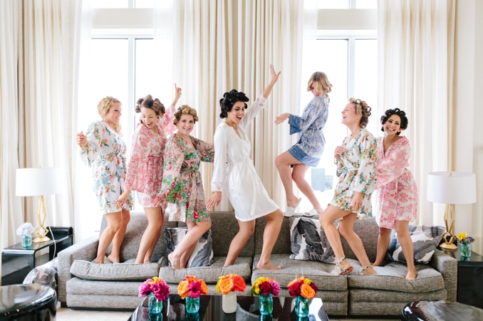 Adorable bridesmaids dancing in their custom robes and curlers in their hair