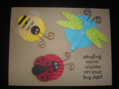 Kraft card with three dimensional bug stickers (bumblebee, dragonfly and ladybug). Each bug is layered on a coordinating punched circle.