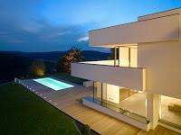 foto de casa moderna con vista a la piscina con luces