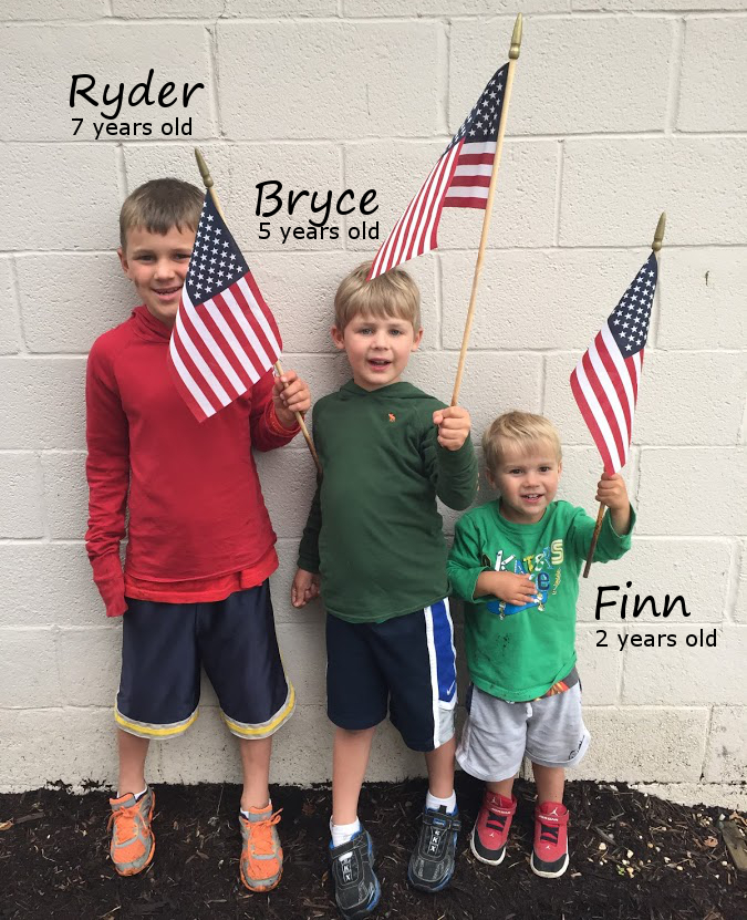 3 boys holding American flags
