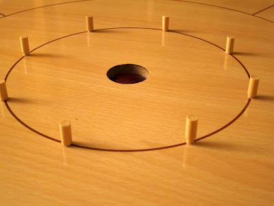 Crokinole - The 8 central wooden peggs. Some fit well whilst others do not!