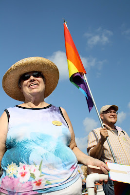 Woman in a large hat and colorful shift stand in the foreground. Behind her her son holds a rainbow pride flag.