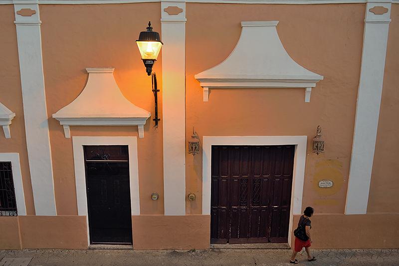 Femme passant devant une maison à l'architecture coloniale à Valladolid