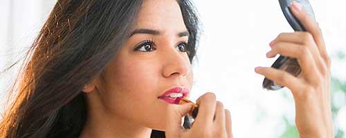 chica maquillandose con pintalabios y espejo