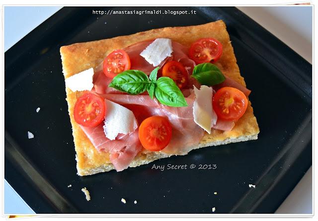 focaccia con lievito madre con la partecipazione di pomodorini, crudo e ricotta salata