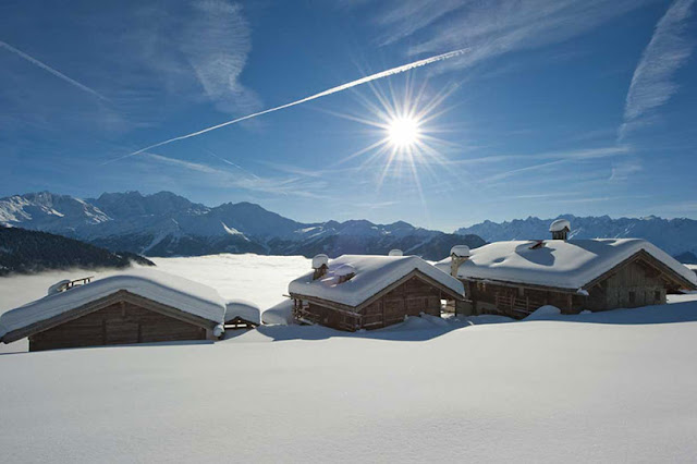 Picture of three wooden houses buried in snow