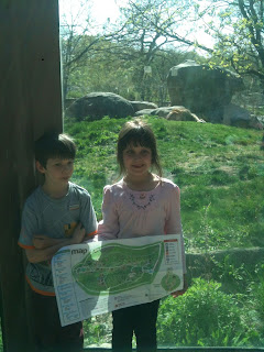 Picture of children holding a map with a lion in the background