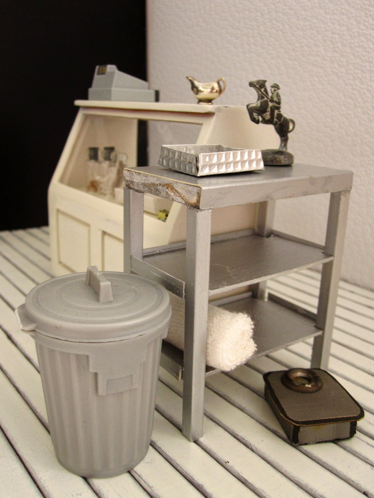 Corner of a modern dolls' house miniature interiors shop, with a range of items in grey, silver and white on display.