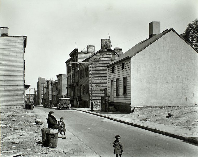 Talman Street, between Jay and Bridge street, Brooklyn. May 22, 1936. Notes: African American woman sits at street edge with two children, empty lots on either side of street, old 2 and 3 story clapboard houses further up. Code: I.A.5.; III.A.4. Source: Changing New York / Berenice Abbott. Repository: The New York Public Library. Photography Collection, Miriam and Ira D. Wallach Division of Art, Prints and Photographs.