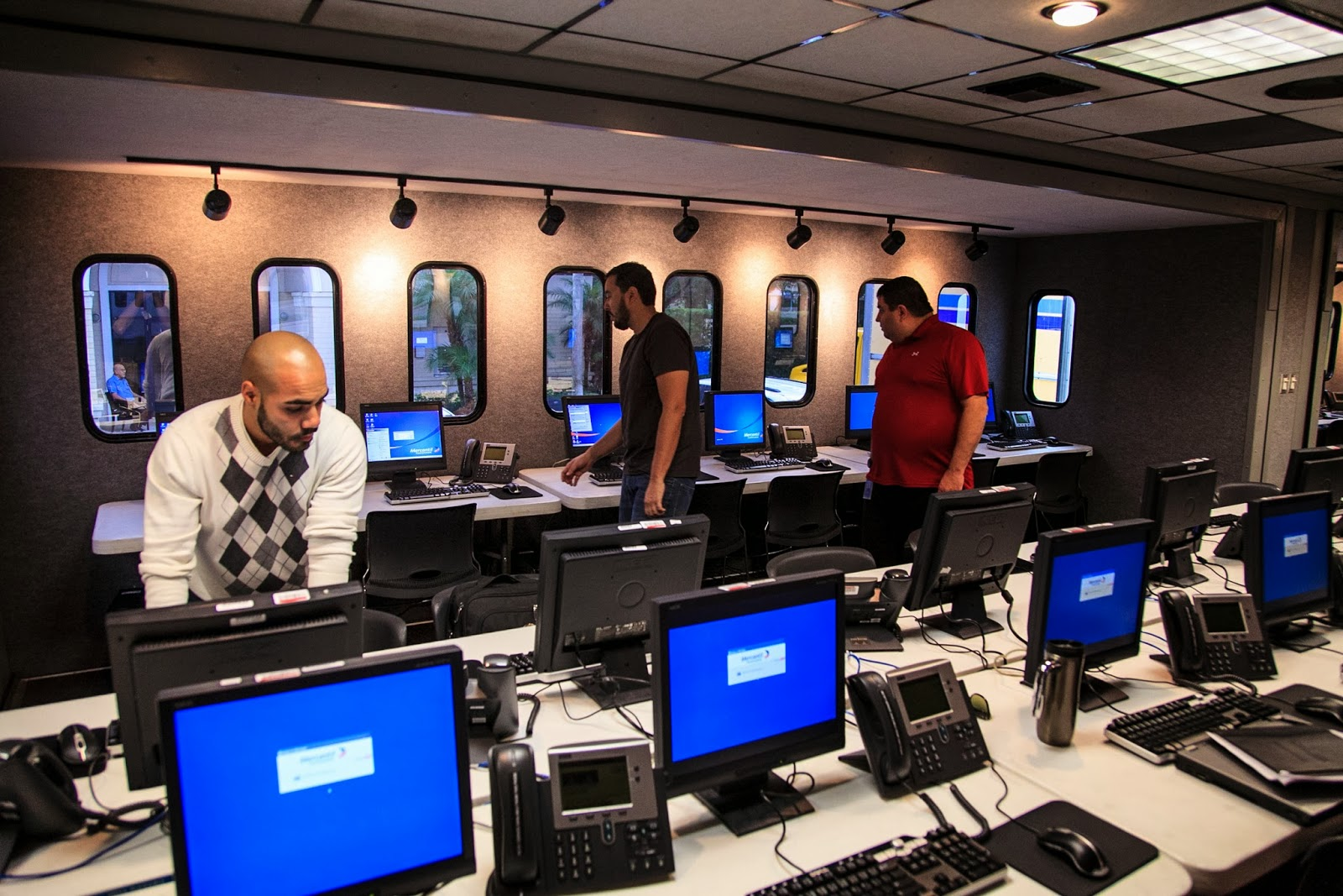 Men setting up computers in mobile workspace