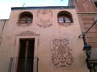 Detall de la façana d'una casa del carrer de Vistalegre amb esgrafiats de temàtica floral i un rellotge de sol
