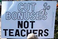 sign saying cut bonus not teachers