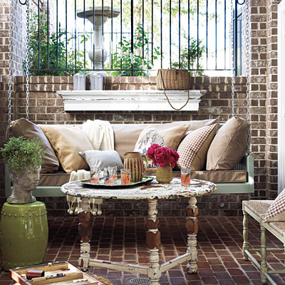 The collection of vintage items on this front porch look lovely agasint the dark brick walls