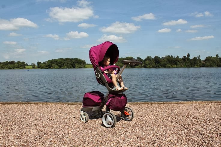 Stokke Xplory with purple textiles on gravel with a matching purple shopping bag and purple changing bag
