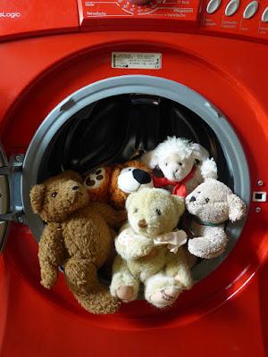 Diverse Stofftiere sitzen im Bullauge einer Waschmaschine