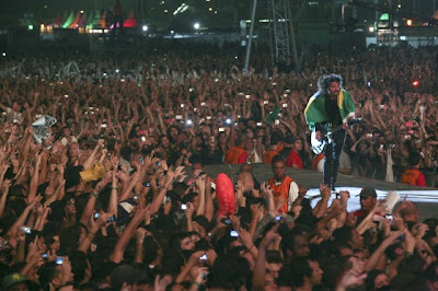 Foto do vocalista do Foo Fighters, Dave Grohl, na passarela em meio ao público em show no Brasil. Vários braços esticados no público, com câmeras e celulares fotografando tudo