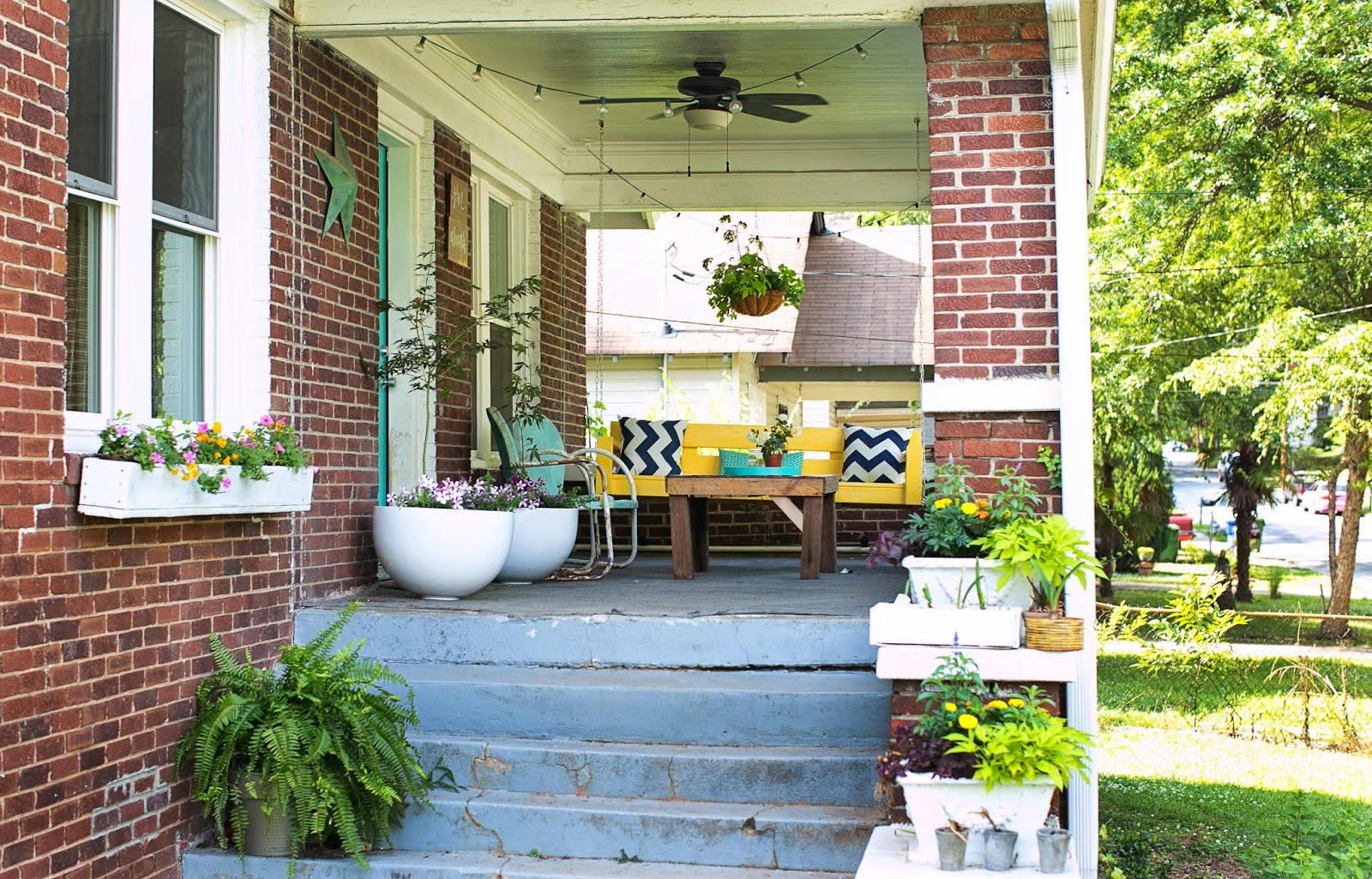 DIY front porch makeover with window boxes, pallet coffee table, yellow swing and turquoise door