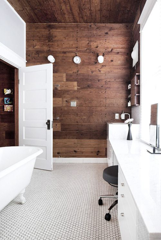 The wooden wall and ceiling are contrasting with the sleek white surfaces in this bathroom designed by Miguel Rivera. Via Inhabitat.