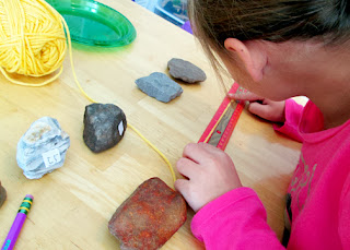 After arranging a selection of rocks by her perception of smallest to largest, Tessa measured the rocks and recorded their actual sizes. To do so, she wrapped pieces of yarn around their widest points, then measured the cut lengths. She was surprised to learn that her perception was drastically off in some cases.