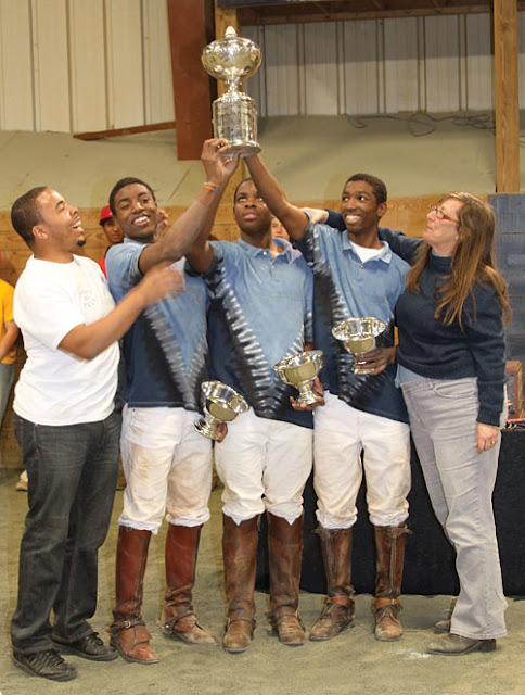 Picture of Polo team work-to-ride holding up championship cup.