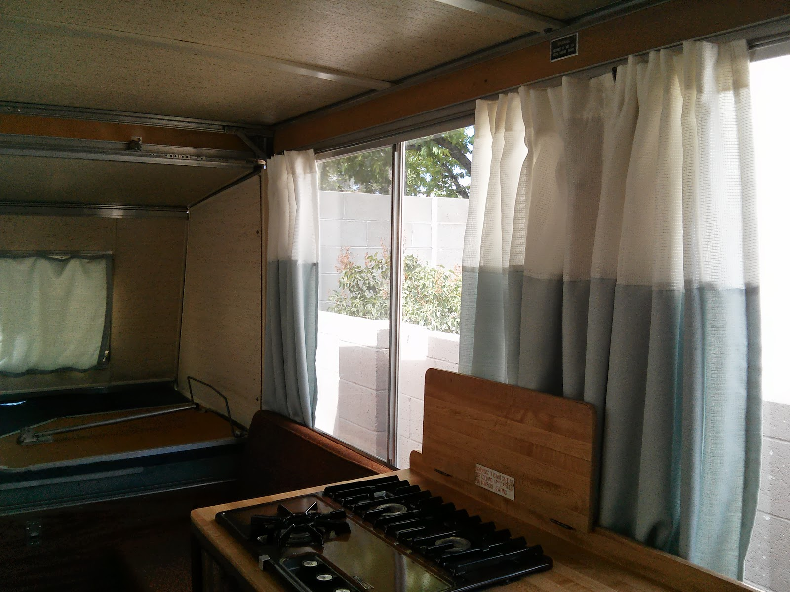 Apache camper interior with new white and blue curtains