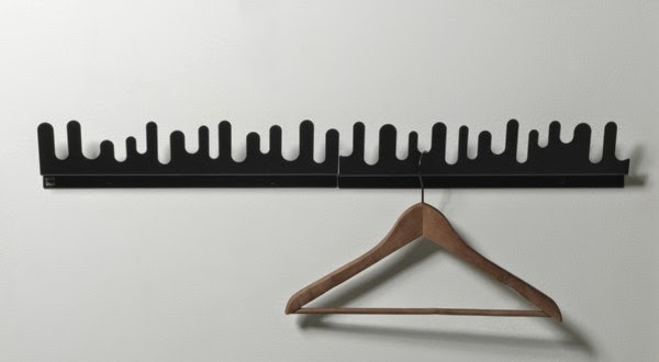 black coat hooks mounted on white wall made of plastic