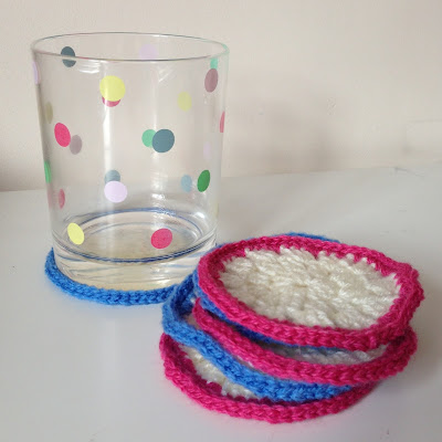 Blue and pink crochet coasters with a spotty tumbler. Pattern by LuluLoves