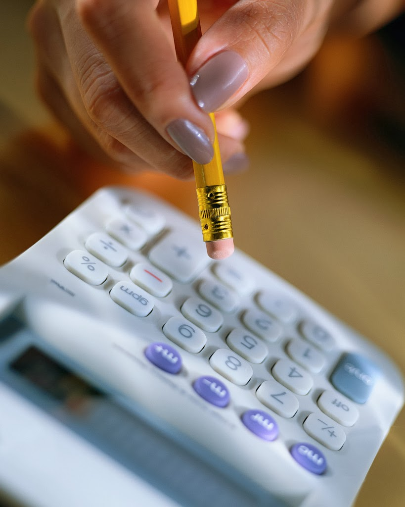Woman using a calculator with pencil