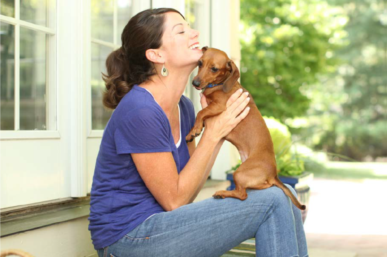 Image of woman holding a small red dachshund dog