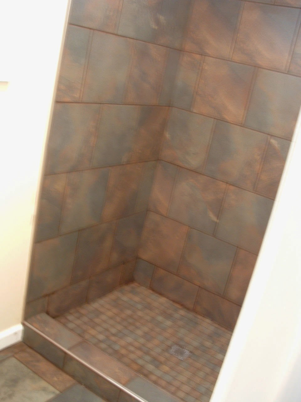 Installed bronze like tile on the weeping wall it looks old school - Guest Bathroom Almost Finished
