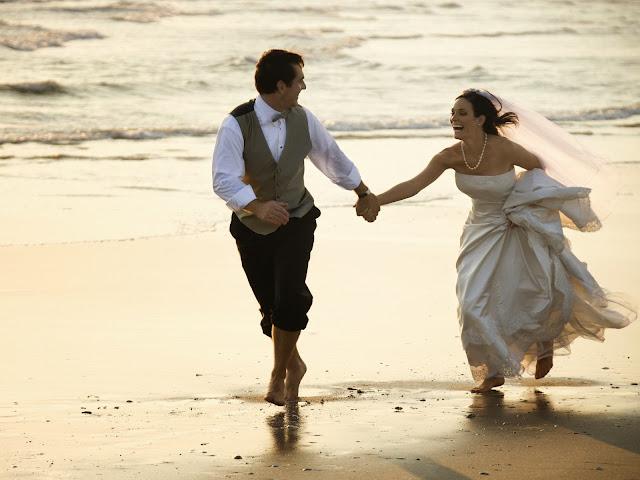 жених и невеста на берегу моря держатся за руки