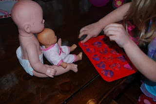 Preschooler using Play Doh to make pretend cookies for her dolls