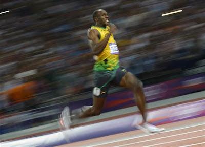 """L'image est celle du grand sprinter Usain Bolt, qui a remporté dernièrement trois médailles d'o raux Jeux Olympiques de Londres en 2012, faisant de lui la star incontestée de ces J.O., en plein effort sur la piste, les deux pieds décollant du sol et portant les désormais célèbres couleurs de la Jamaïque, le jaune pour le maillot et le vert pour le short. Cette photographie du grand champion et recordman du monde sur 100 mètres, 200 mètres et du relai 4x100 Usain Bolt illustre le poème """"On m'a dit"""" d'un autre champion dans son domaine et tout aussi célèbre, le grand poète Le Marginal Magnifique. Dans ce poème il est question de morale, de toutes ces choses que l'on s'entend dire lorsque l'on est enfant. Chaque strophe débute ainsi par les mots """"On m'a dit"""" en une sorte de litanie qui mime la répétition de ces paroles moralisatrices que l'on entend au cours de notre vie. Le Marginal Magnifique, loin d'approuver ces paroles consensuelles, les tourne en dérision en montrant qu'elles ne contribuent pas au bonheur, qu'elle n'exprime nullement l'essence de la vie, tout au plus l'essence d'une société aseptisé, castratrice et créatrice de robots formatés, ce qui est complètement différent. Une de ces vérités que la morale n'apprend pas et qui semble chère au poète est tout simplement que la vie est très courte et qu'il faut en profiter sans se soucier justement de la morale. Le Marginal Magnifique exprime cela en une image saisissante disant que la vie court plus vite qu'Usain Bolt sur cent mètres et qu'il faut la saisir par le maillot, ce qui n'est pas chose aisée, mais qu'il faut s'efforcer de faire."""