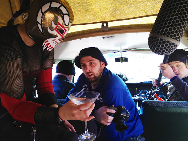 A Mexican wrestler holding a martini inside a Volkswagen van during a flim shoot.