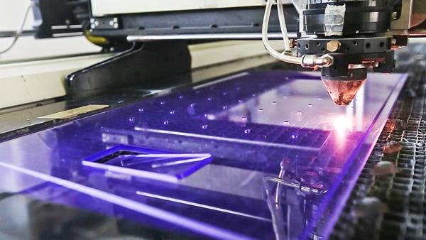 Macchina taglia una lastra di plexiglass