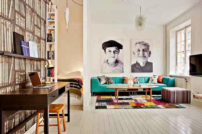 Skandynawskie wnętrze, podłoga z białych desek, turkusowa sofa, kolorowy dywan, portrety na ścianie, czarne biurko