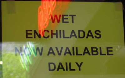 Yellow handmade sign reading WET ENCHILADAS NOW AVAILABLE DAILY