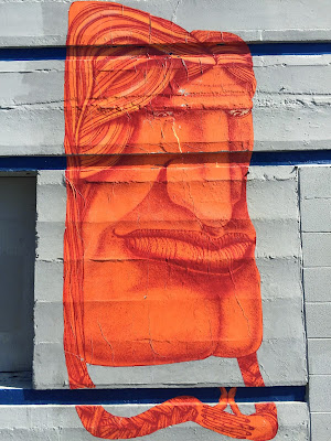 Orange paste-up face on NW Dock Pl Ballard.