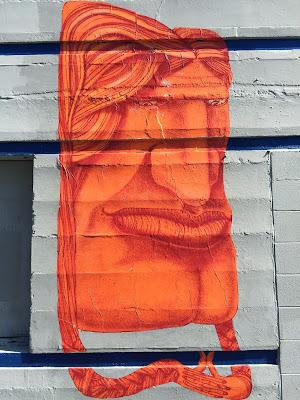Orange paste-up face on NW Dock Pl Ballard.